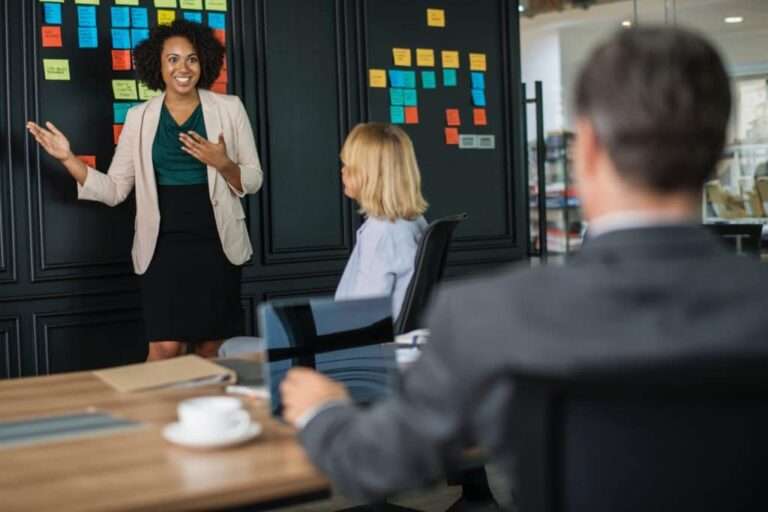 digital marketing consultant image showing a standing woman enthusiastically discussing a presentation to a group of executives