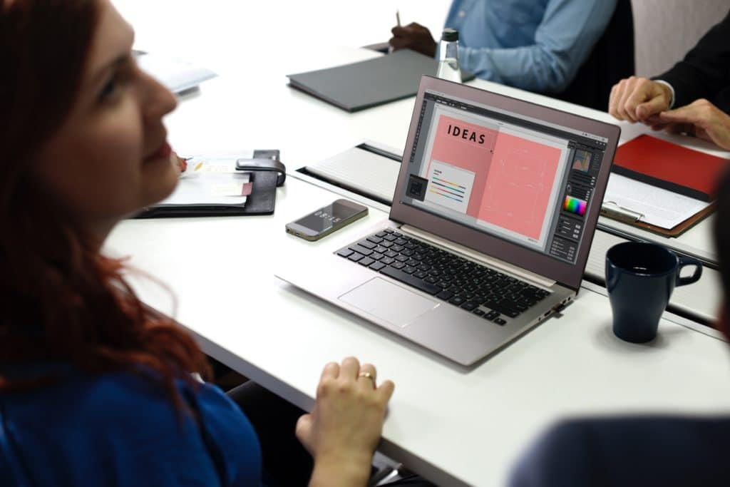 """website design services image showing a woman in front of a laptop with the word """"IDEAS"""" on the screen"""