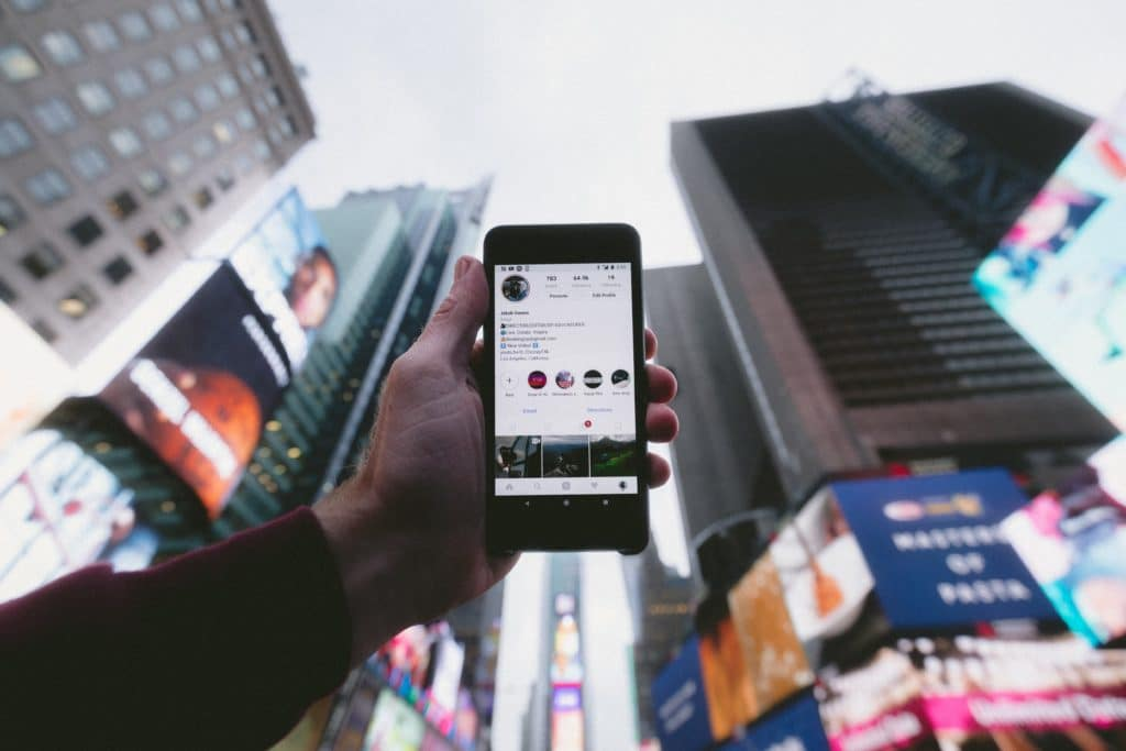 search engine optimization services image of a person surrounded by skyscrapers showing their smartphone's screen