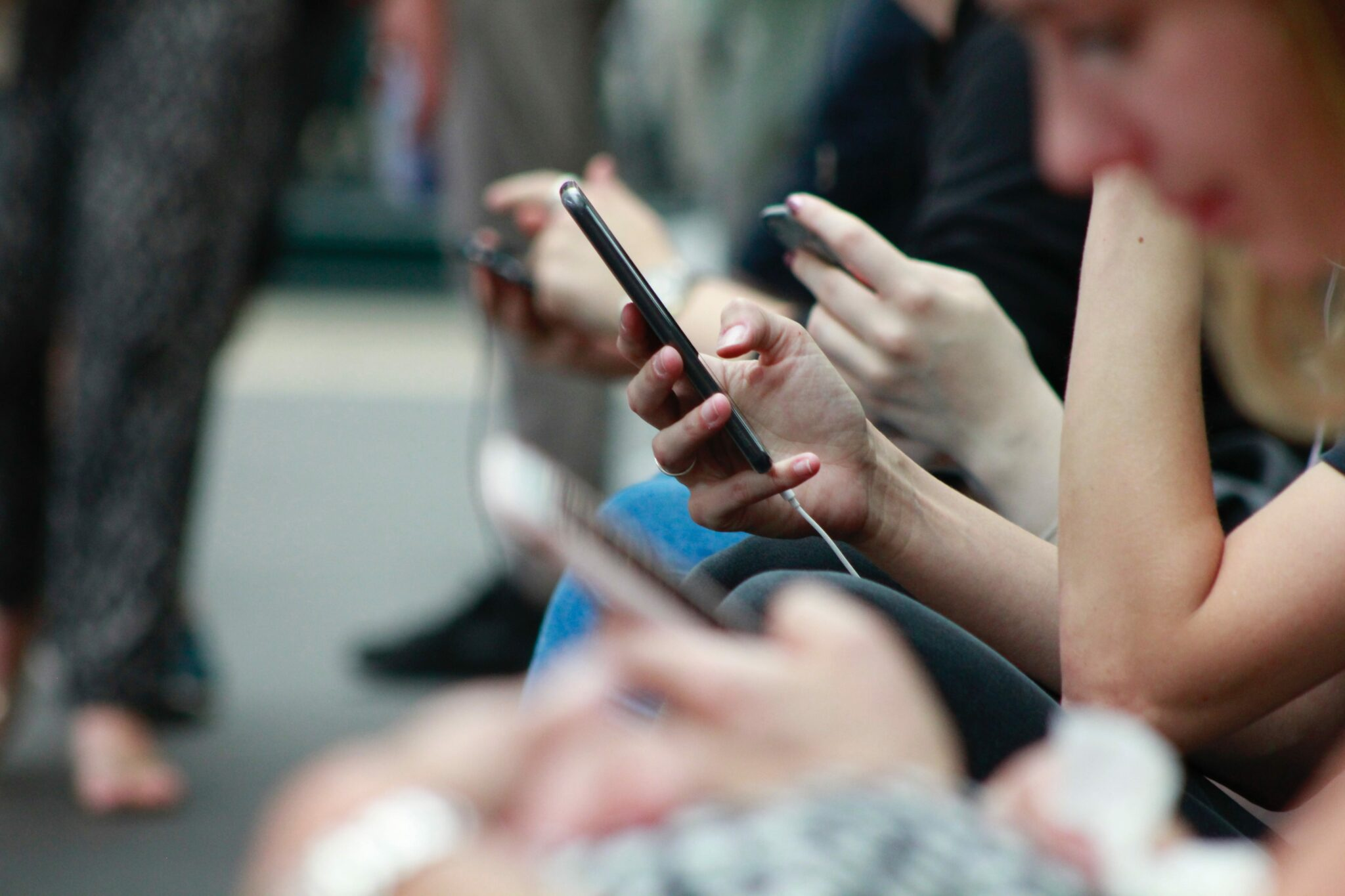 A line of people all holding Smartphones